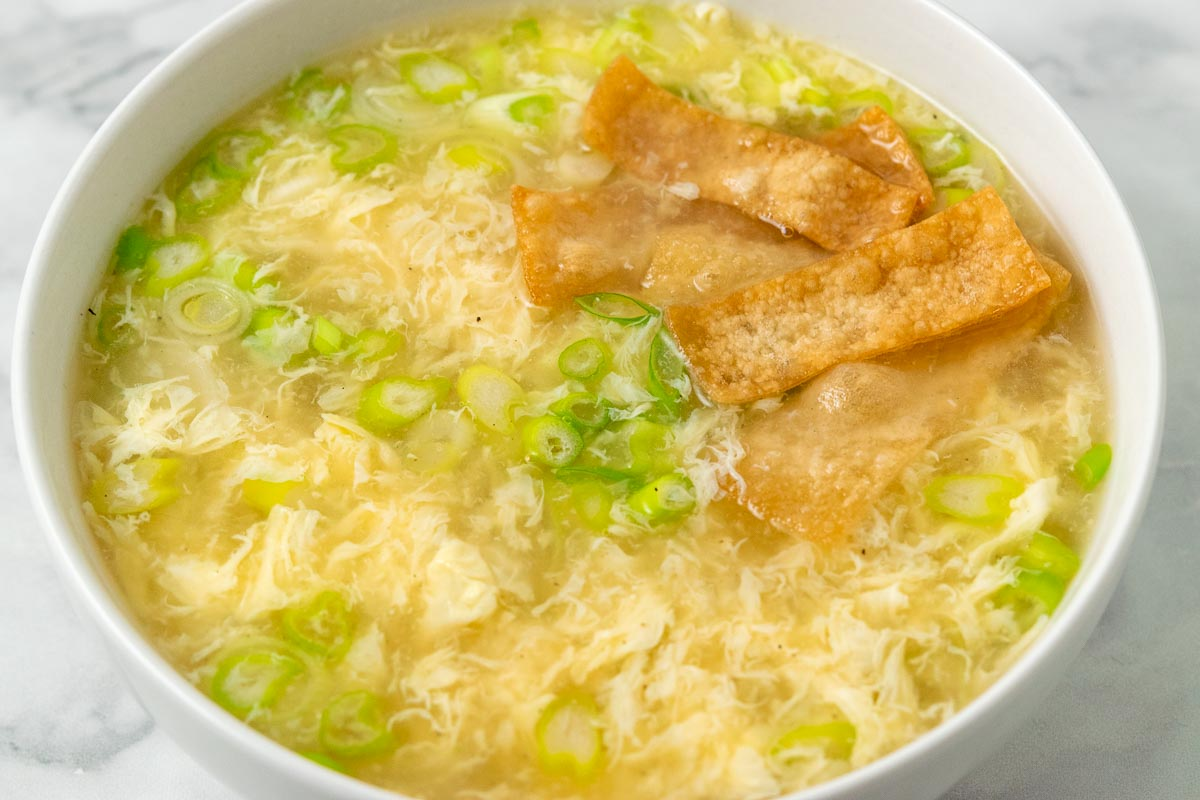 a bowl of egg drop soup with green onions and crispy wonton croutons.