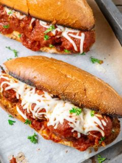 two homemade meatball subs on a baking sheet.