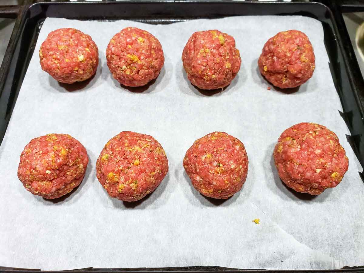 8 uncooked meatballs on a baking sheet.