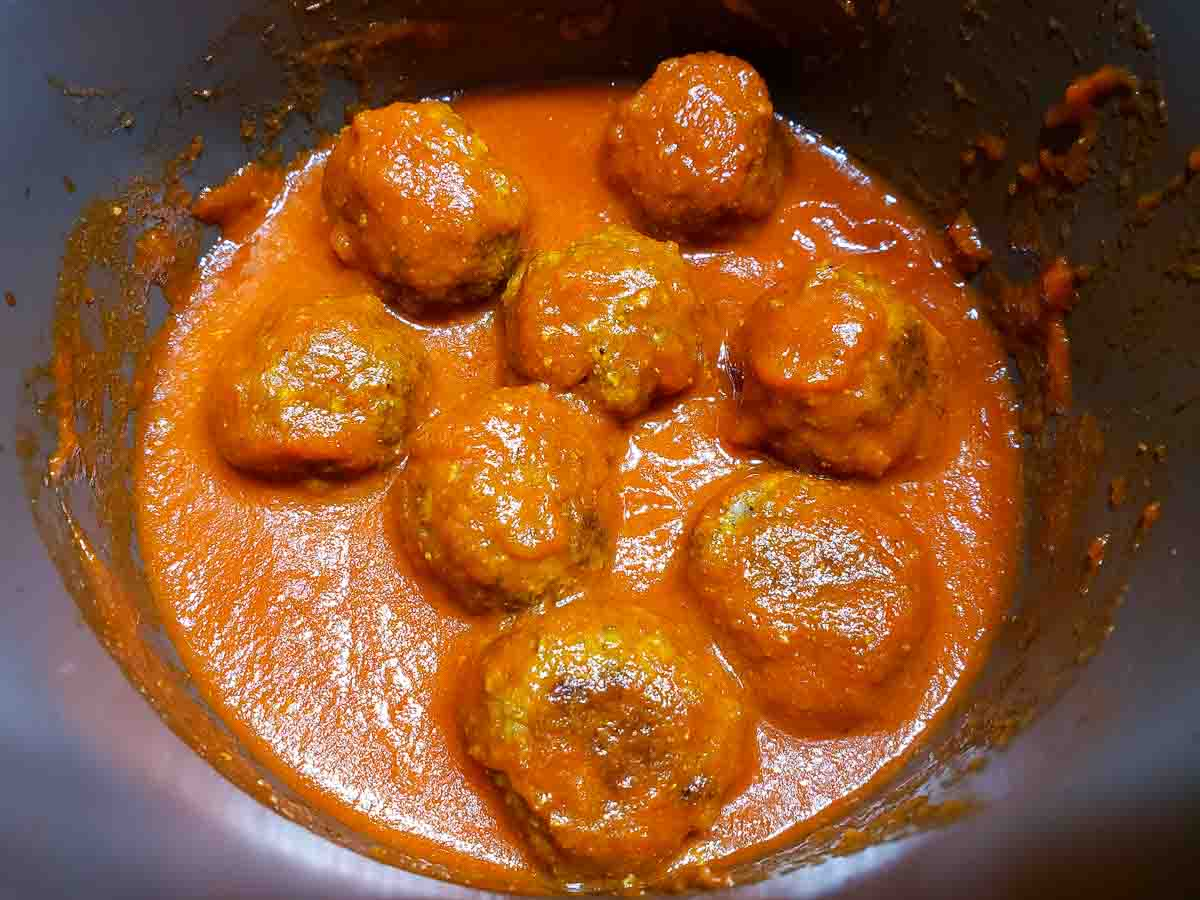 meatballs and red spaghetti sauce in a pan.
