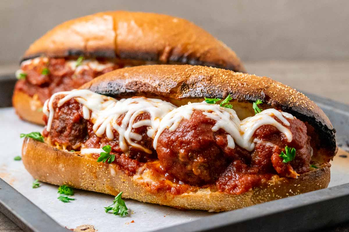 two meatball sandwiches on a baking sheet.