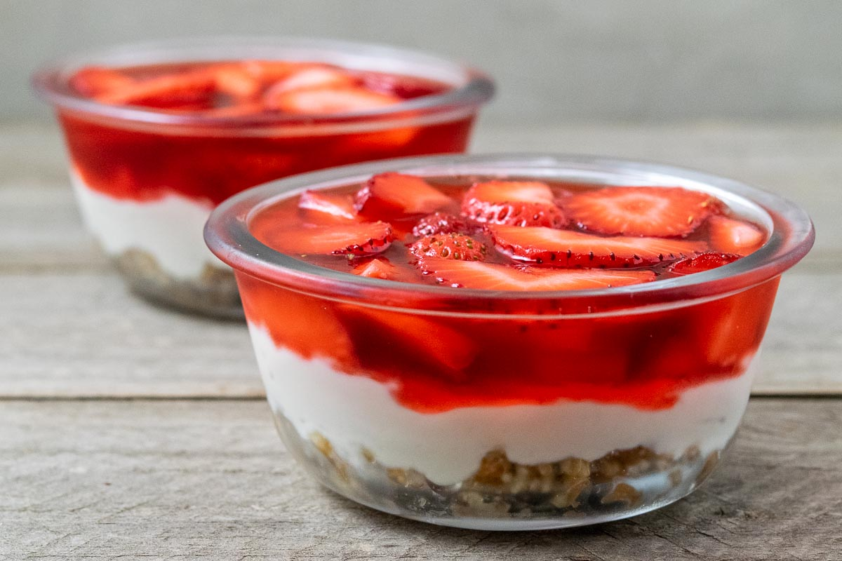 two bowls filled with strawberry pretzel dessert in two bowls.