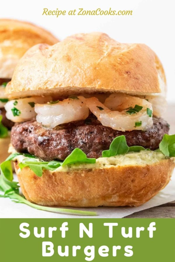 two burger buns filled with beef patties, arugula, pesto mayo, and seared shrimp and text reading recipe at zonacooks.com surf n turf burgers.