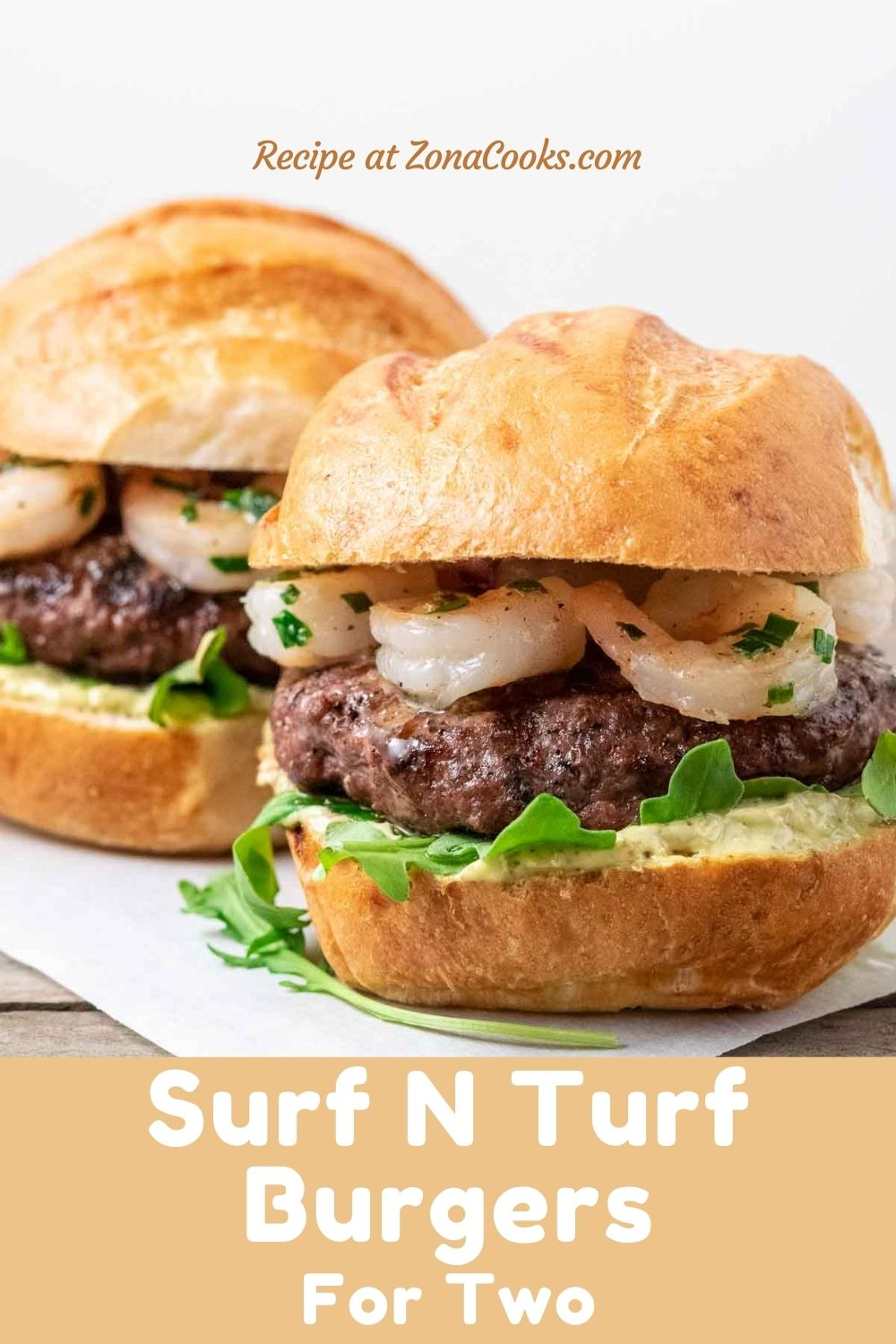 two burger buns filled with beef patties, arugula, pesto mayo, and seared shrimp and text reading recipe at zonacooks.com surf n turf burgers for two.