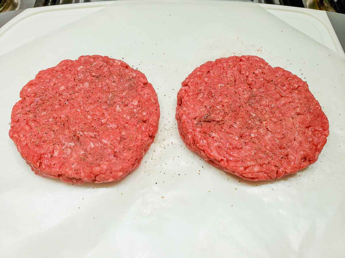 two ground sirloin beef patties sprinkled with salt and pepper.