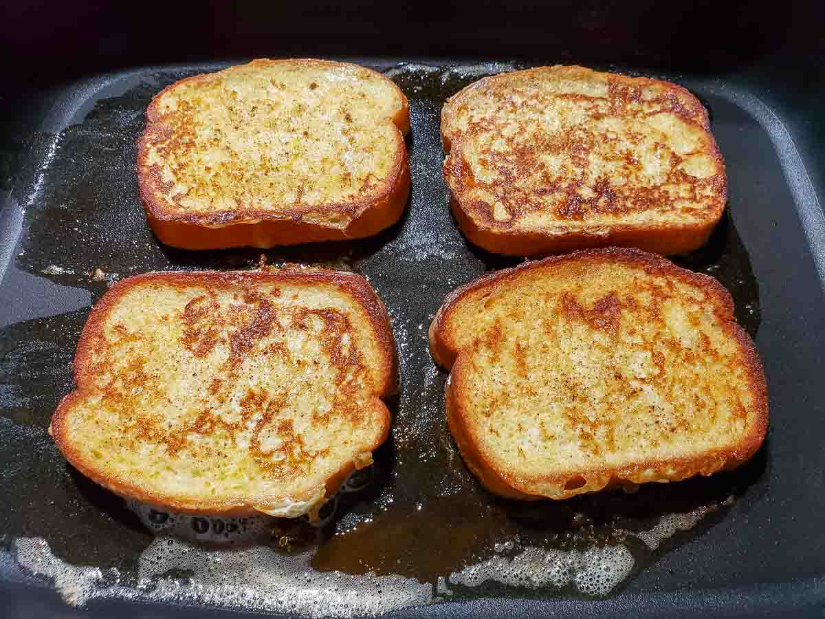 four slices of texas toast french toast frying in an electric skillet.