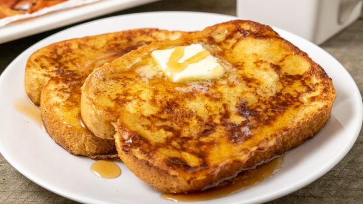 two thick slices of texas toast french toast topped with butter and syrup with a side of bacon and milk.
