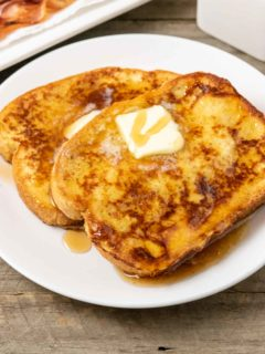 two thick slices of texas toast french toast topped with butter and syrup and a side of bacon.