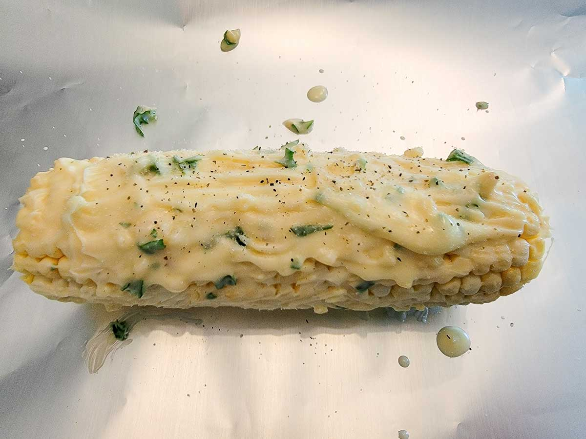 one ear of corn on the cob slathered with butter, garlic, salt, pepper, and parsley.