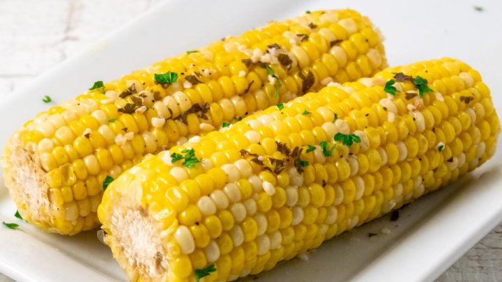 two ears of slow cooker corn on the cob on a plate.