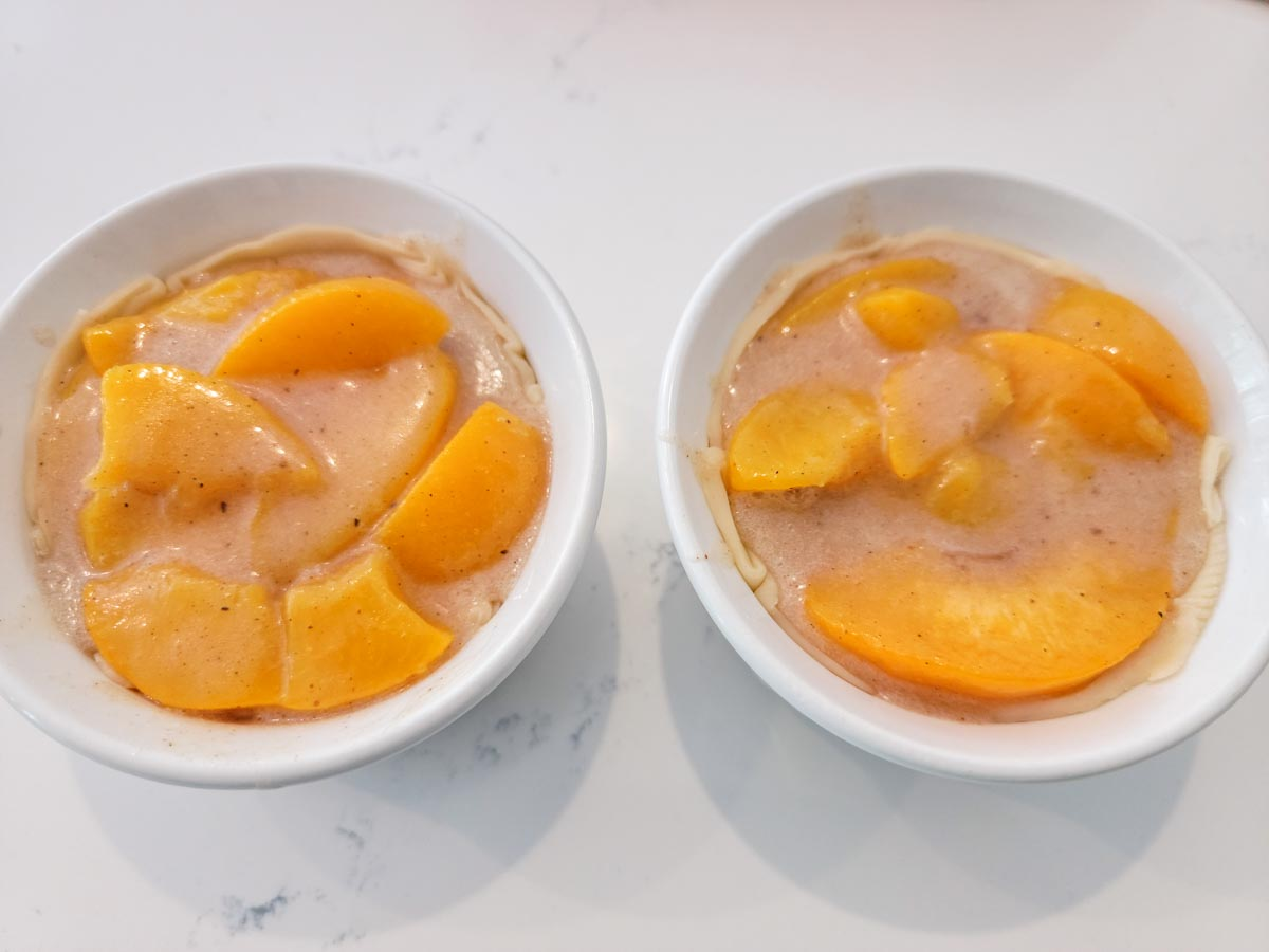 two ramekins filled with pie crust and peach pie filling.