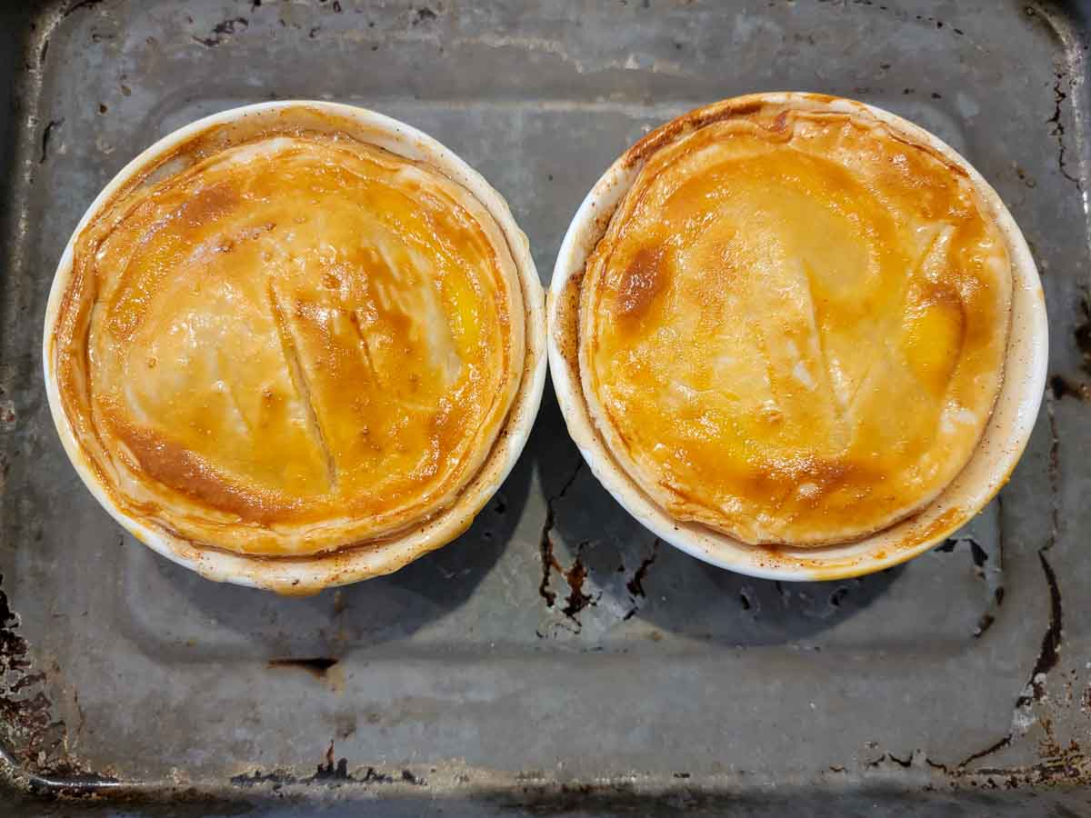 two baked mini pies on a baking sheet.