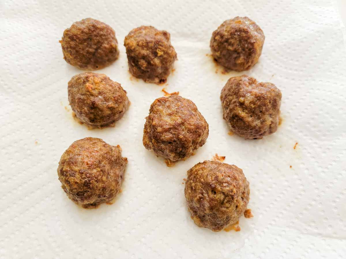 8 baked meatballs draining on paper towel.