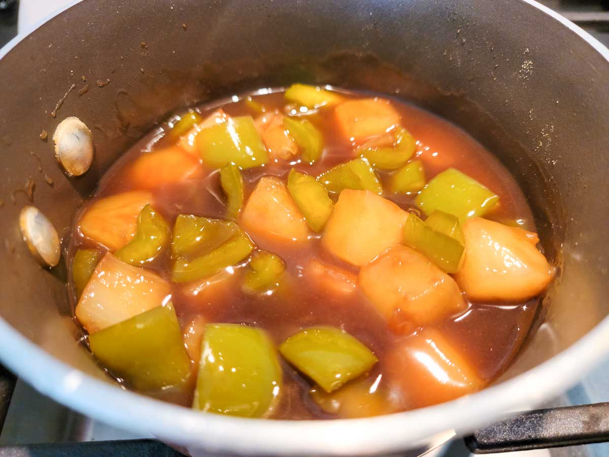 a sauce pan filled with pineapples, green peppers and brown sauce with cornstarch slurry stirred in.