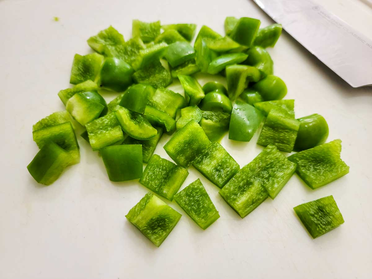 green peppers diced on a cutting board.
